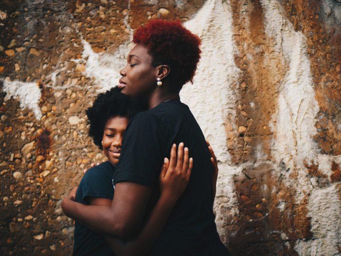 Mother hugging teen daughter