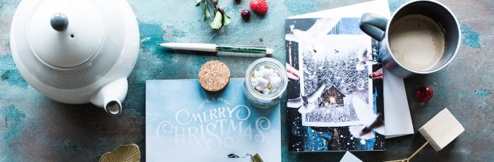 Clutered desk with holiday card and tea pot